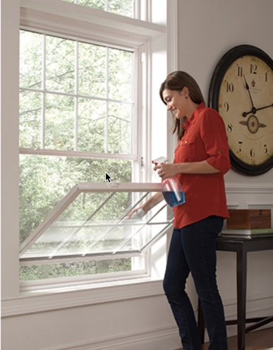 woman cleaning a double hung window
